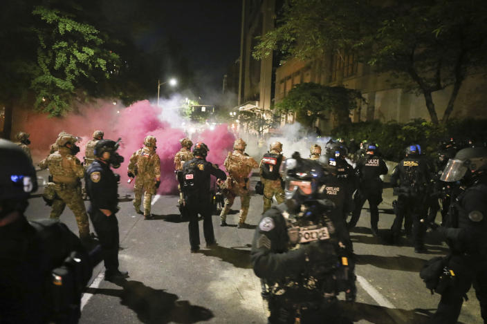 Police respond to protesters during a demonstration, Friday, July 17, 2020 in Portland, Ore. Militarized federal agents deployed by the president to Portland, fired tear gas against protesters again overnight as the city's mayor demanded that the agents be removed and as the state's attorney general vowed to seek a restraining order against them. (Dave Killen/The Oregonian via AP)