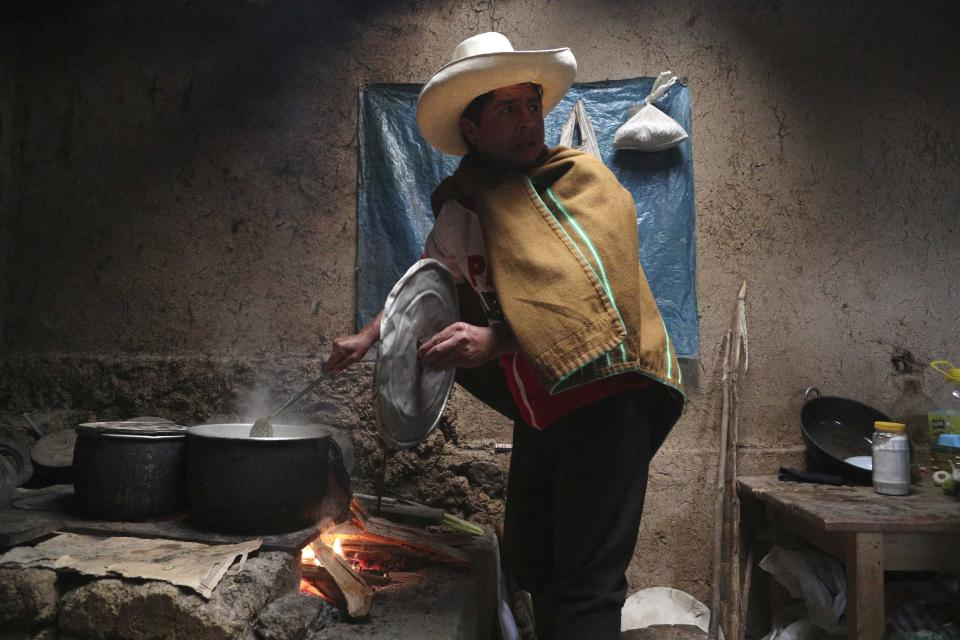 Free Peru party presidential candidate Pedro Castillo cooks breakfast for his family in his home in Chugur, Peru, Friday, April 16, 2021. Castillo, a rural teacher, who has proposed rewriting Peru's constitution and deporting all immigrants living in the country illegally who commit crimes, will face rival candidate Keiko Fujimori in the June 6 presidential run-off election. (AP Photo/Martin Mejia)