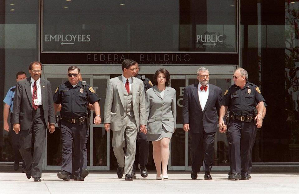Former White House intern Monica Lewinsky is escorted by police officers, federal investigators and her attorney William Ginsburg as she leaves the Federal Building on 28 May 1998 in Westwood, California, after submitting new evidence to Kenneth Starr's office (VINCE BUCCI/AFP via Getty Images)