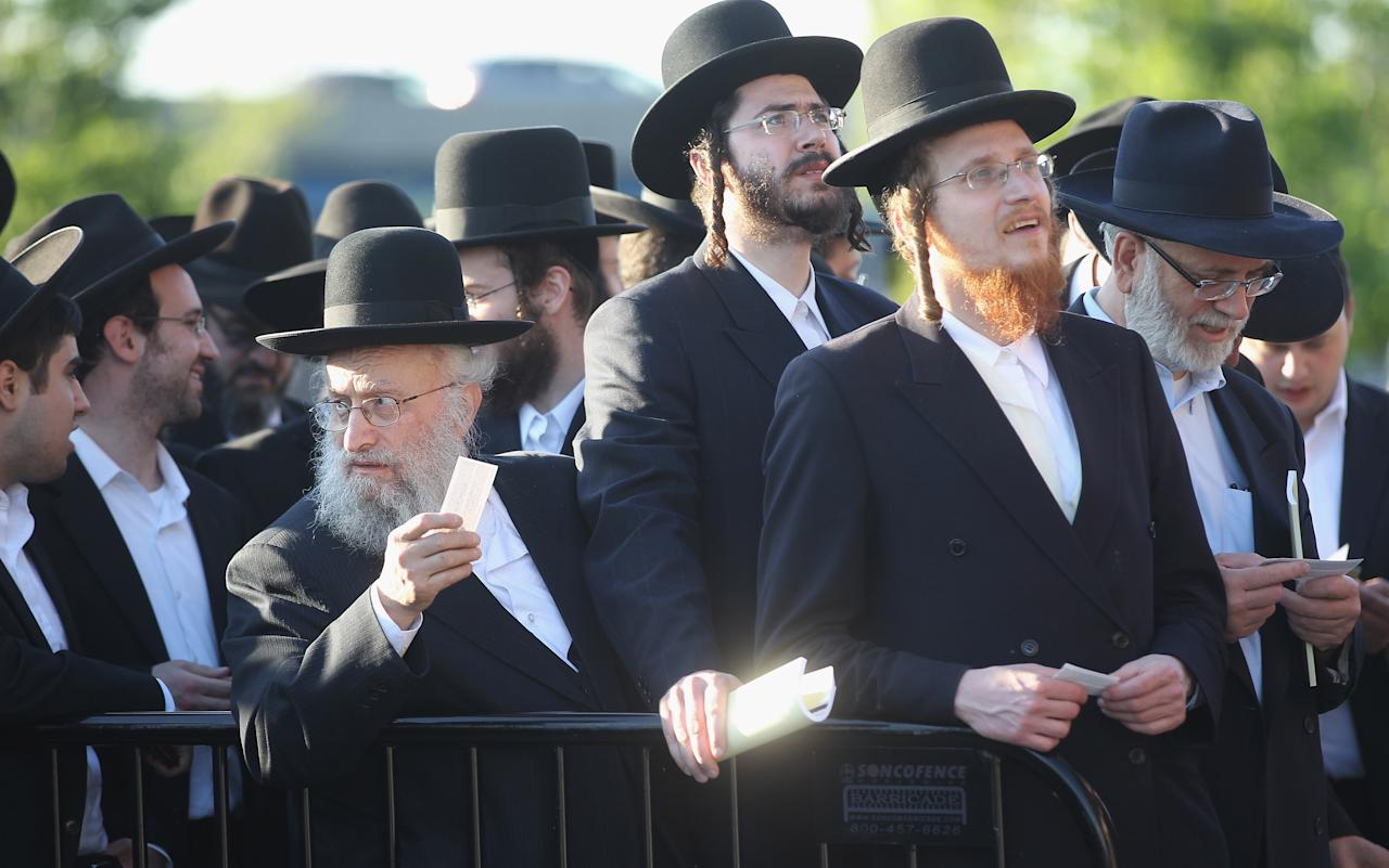 Ultra-Orthodox Jews wait to enter Citi Field for a meeting to discuss the risks of using the Internet on May 20, 2012 in the Queens borough of New York City. More than 40,000 were expected to attend the rally at Citi Field, the home of the New York Mets, which organizers said would promote religiously responsible ways to use the Internet.  (Photo by Mario Tama/Getty Images)