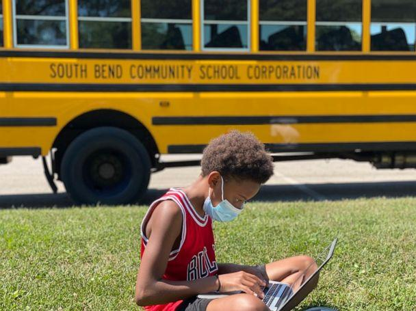 PHOTO: Tre'Vonne Wallace, an eighth grader at Navarre Middle School in South Bend, Ind., sits with a computer outside one of South Bend Community School Corporation's Wi-Fi buses. (Monica Leyes/South Bend Community School Corporation)