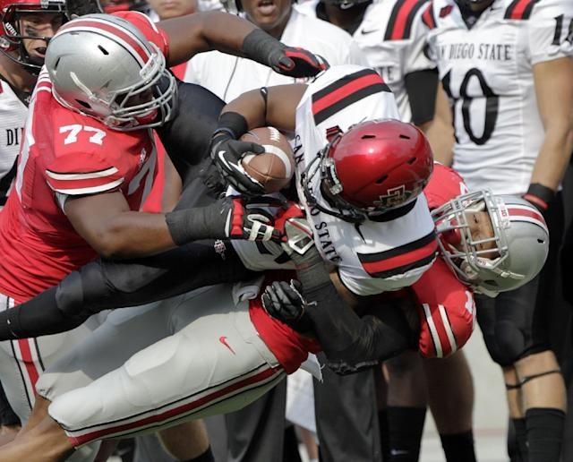 San Diego State running back Chase Price, center, is tackled by Ohio State linebacker Ryan Shazier, right, and defensive lineman Michael Hill during the second quarter of an NCAA college football game Saturday, Sept. 7, 2013, in Columbus, Ohio. (AP Photo/Jay LaPrete)