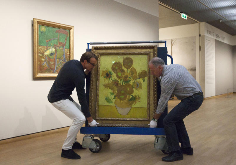 """Curators are putting Vincent van Gogh's famous """"Sunflowers"""" painting onto a felt-lined carrier trolley at the Van Gogh Museum in Amsterdam, Netherlands, Sunday, Sept. 23, 2012. While the museum closes for seven months for renovations, 75 works by the Dutch painter will be displayed instead across town at The Hermitage, an Amsterdam satellite of the Russian state museum. The tricky process of transporting the artworks under police escort began immediately after the last visitors left the museum Sunday evening and carried on through the night into Monday morning. The Van Gogh Museum reopens April 25, 2013. (AP Photo/Cris Toala Olivares)"""