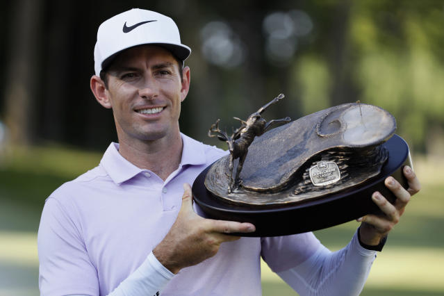 Dylan Frittelli, of South Africa, holds the trophy after winning the John Deere Classic golf tournament, Sunday, July 14, 2019, at TPC Deere Run in Silvis, Ill. (AP Photo/Charlie Neibergall)