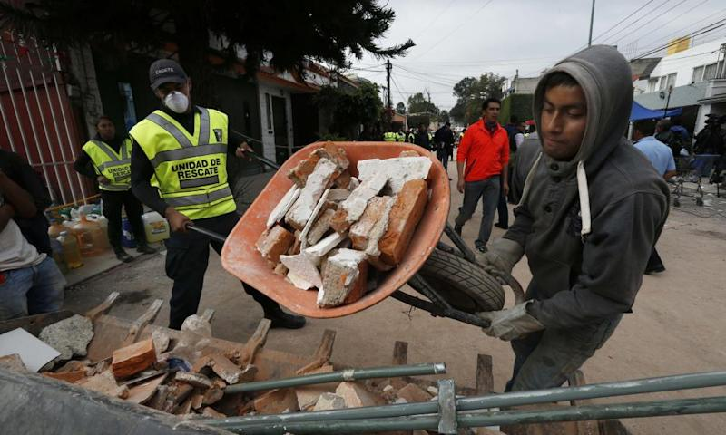 A man moves rubble taken from the Enrique Rebsamen school that collapsed after an earthquake in Mexico City.