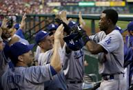 Los Angeles Dodgers' Dee Gordon, right, is congratulated by teammates in the dugout after scoring on single by Jerry Hairston Jr. during the second inning of a baseball game against the St. Louis Cardinals on Wednesday, Aug. 7, 2013, in St. Louis. (AP Photo/Jeff Roberson)