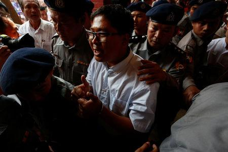 Detained Reuters journalist Wa Lone is escorted by police while arriving for a court hearing after a lunch break in Yangon, Myanmar February 21, 2018. REUTERS/Stringer