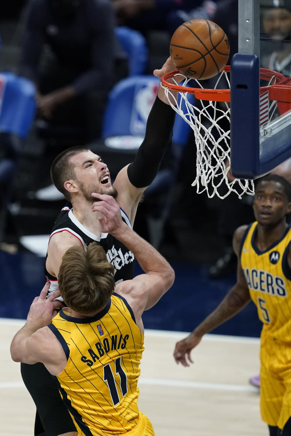 Los Angeles Clippers' Ivica Zubac (40) dunks over Indiana Pacers' Domantas Sabonis (11) during the first half of an NBA basketball game, Tuesday, April 13, 2021, in Indianapolis. (AP Photo/Darron Cummings)