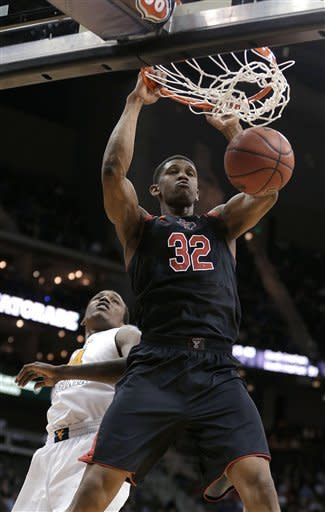 Texas Tech forward Jordan Tolbert (32) dunks in front of West Virginia center Aaric Murray (24) during the second half an NCAA college basketball game in the Big 12 men's tournament Wednesday, March 13, 2013, in Kansas City, Mo. Texas Tech won 71-69. (AP Photo/Charlie Riedel)