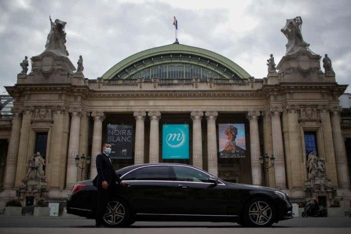 A chauffeur poses next to a Mercedes-Benz luxury car of Chabe, Chauffeured Cars Services, in front of the Grand Palais in Paris