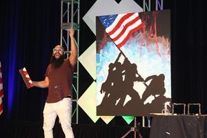 Joe Everson shows off the end result of his painting that he did live while singing the National Anthem.