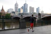 A solitary man runs along a waterway under COVID-19 lockdown restrictions in Melbourne