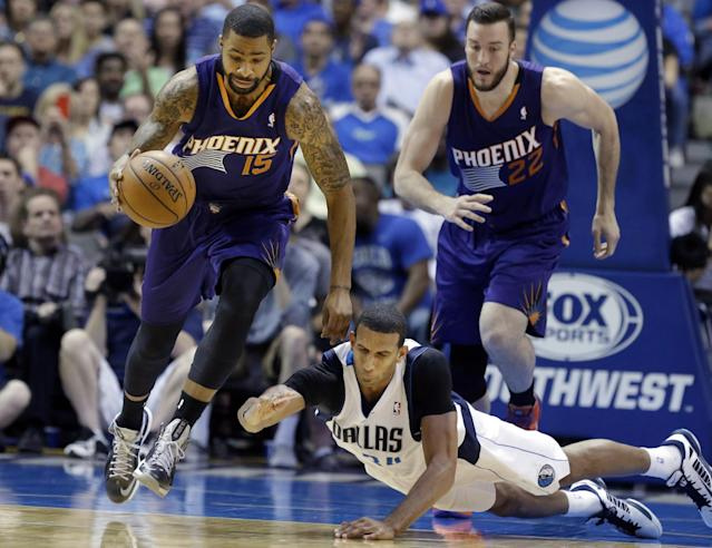 Phoenix Suns forward Marcus Morris (15) comes up with the ball against Dallas Mavericks forward Brandan Wright (34) as Suns' Miles Plumlee (22) runs up during the first half of an NBA basketball game on Saturday, April 12, 2014, in Dallas. (AP Photo/LM Otero)
