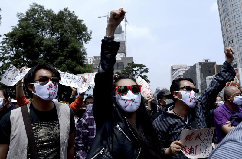 """Chinese people wear face masks with """"No to Kunming PX,"""" paraxylene, written, chant slogans as they hold protest against a planned refinery project in downtown Kunming in southwest China's Yunnan province Saturday, May 4, 2013. After word spread about an environmental protest that was planned for Saturday in the central Chinese city of Chengdu, drugstores and printing shops were ordered to report anyone making certain purchases. Microbloggers say government fliers urged people not to demonstrate, and schools were told to stay open to keep students on campus. Meanwhile, hundreds of people - many wearing mouth masks - gathered in Kunming to protest a planned refinery project in the area. The demonstrators demanded information transparency and that public health be safeguarded. (AP Photo) CHINA OUT"""