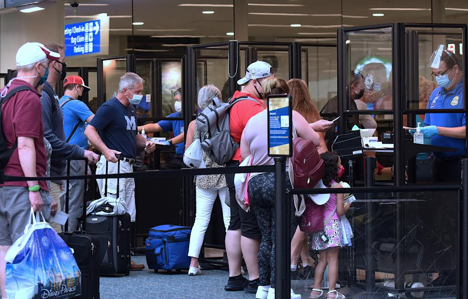 ORLANDO, FLORIDA, UNITED STATES - 2021/05/01: Travelers wearing face masks as a preventive measure against the spread of covid-19 wait in line to be screened by TSA at Orlando International Airport.