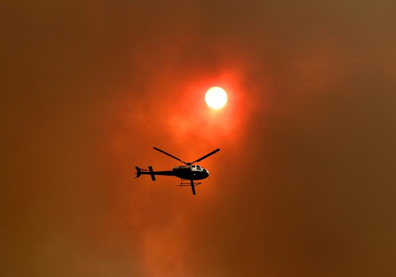 A spotter helicopter flies through thick bushfire smoke in Nana Glen, near Coffs Harbour, Tuesday, November 12, 2019. There are more than 50 fires burning around the state, with about half of those uncontained. (AAP Image/Dan Peled) NO ARCHIVING