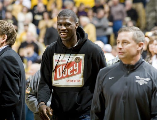 """Football recruit Dorial Green-Beckham, left, smiles as the crowd chants """"MIZ-DGB"""" as he arrives courtside just before the Missouri-Texas Tech NCAA college basketball game Saturday, Jan. 28, 2012, in Columbia, Mo. He was escorted by Missouri assistant coach Andy Hill, right, before the game (AP Photo/L.G. Patterson)"""