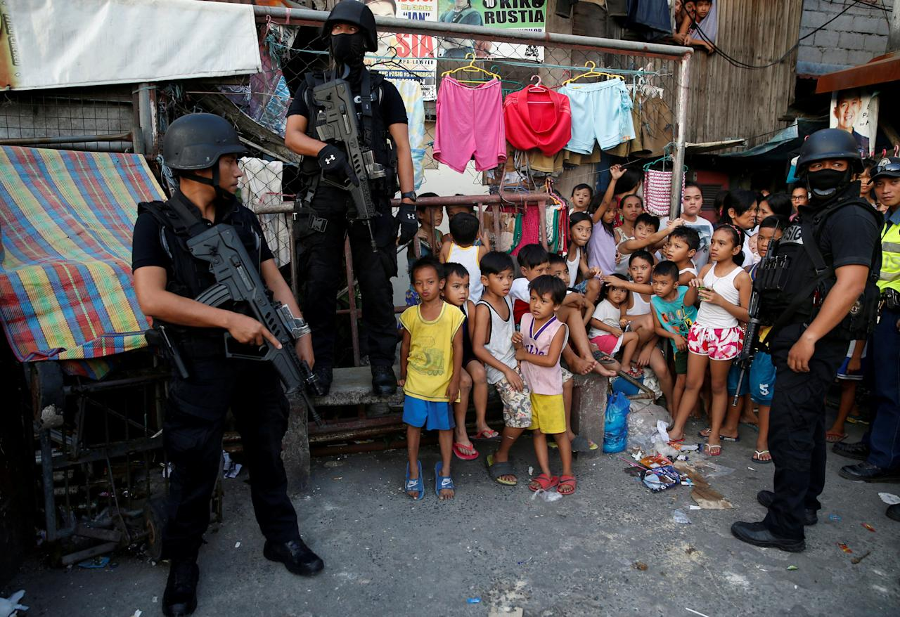 FILE PHOTO: Members of Philippine National Police SWAT team stand guard near the residents during an anti-drugs operation, in Pasig, Metro Manila in the Philippines, November 9, 2016.  REUTERS/Erik De Castro/File Photo