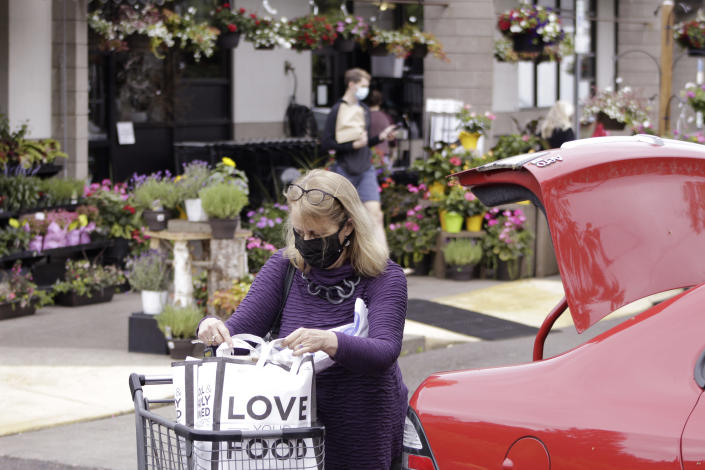 A woman wearing a face mask loads groceries into her car after shopping at a Zupan's grocery store in Portland, Ore., on Friday, May 21, 2021. As the federal government and many states ease rules around mask-wearing and business occupancy, some blue states like Oregon and Washington are still holding on to some longtime coronavirus restrictions. (AP Photo/Gillian Flaccus)