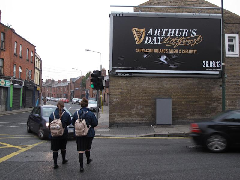 Morning commuters and two schoolgirls pass a billboard advertising Arthur's Day in Dublin, Ireland, on Thursday, Sept. 26, 2013. Ireland's love affair with pub and pint is sparking national soul-searching as never before because of an unofficial holiday dreamed up by Guinness. Thursday's celebrations of Arthur's Day, honoring the 18th-century founder of Ireland's quintessential drink, feature surprise musical performances in 815 pubs and clubs across Ireland as well as concerts worldwide from Malaysia to Jamaica. (AP Photo/Shawn Pogatchnik)