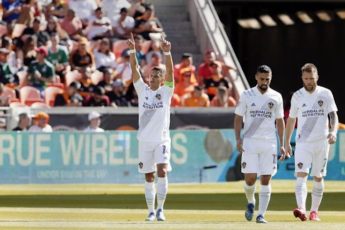 """LA Galaxy forward Javier """"Chicharito"""" Hernandez, left, reacts after a score as he and midfielders Sebastian Lletget (17) and Aleksandar Katai (7) walk back to midfield during the first half of an MLS soccer match against the Houston Dynamo, Saturday, Feb. 29, 2020, in Houston. (AP Photo/Michael Wyke)"""