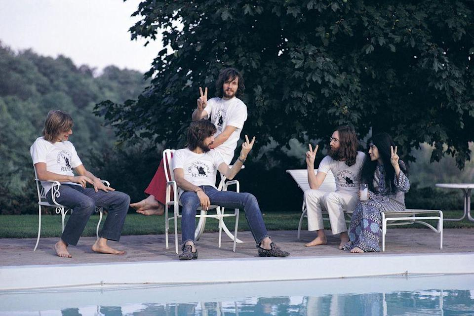 """<p>Eric Clapton (center, seated) debates how to make the """"peace"""" sign with John Lennon and Yoko Ono at a pool in 1969.</p>"""