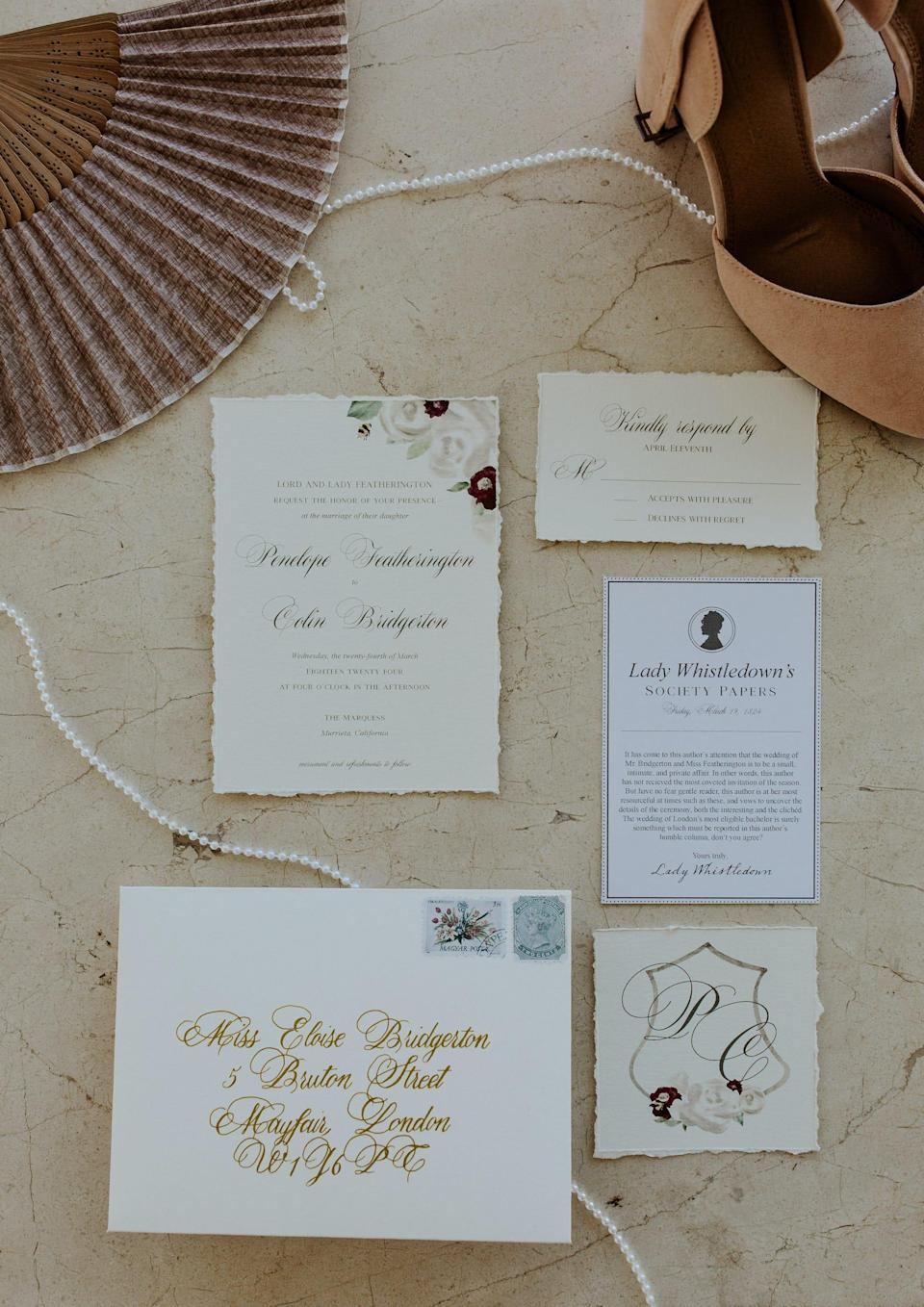 Wedding invitations sit on a table next to a fan, a string of pearls, and a tan shoe.