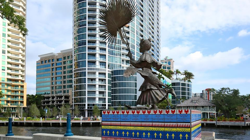 """FORT LAUDERDALE, FL - MAY: Tall life-sized bronze statue titled """"Florida, a Seminole Girl"""" located at Stranahan Landing, directly across the New River from the Stranahan House as seen May 10, 2018."""