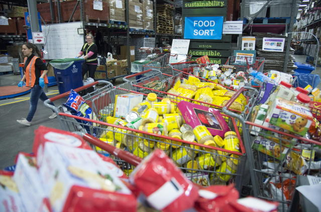 Staff at the Greater Vancouver Food Bank prepare food in Burnaby, British Columbia, Wednesday, March 18, 2020. (Jonathan Hayward/The Canadian Press via AP)