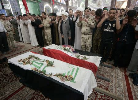 Mourners pray in front of the coffins of Shi'ite volunteers, who had joined the Iraqi Army and were killed during clashes with militants of the Islamic State, formerly known as the Islamic State of Iraq and the Levant (ISIL), during a funeral in Kerbala, southwest of Baghdad, July 12, 2014. REUTERS/Mushtaq Muhammed