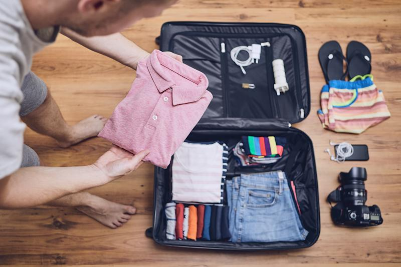 Man Packing Clothes In Luggage At Home
