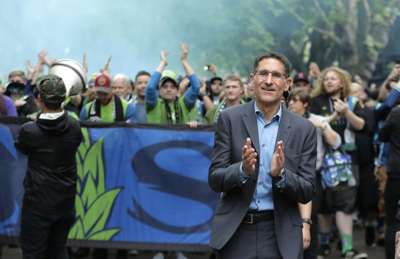 FILE - In this June 30, 2018, file photo, Seattle Sounders owner Adrian Hanauer, right, takes part in the traditional March to the Match before an MLS soccer match between the Sounders and the Portland Timbers in Seattle. The Sounders announced Tuesday, Aug. 13, 2019, that they are adding Seattle Seahawks quarterback Russell Wilson and several others to the club's ownership group, as Hollywood producer Joe Roth leaves the franchise. (AP Photo/Ted S. Warren, File)