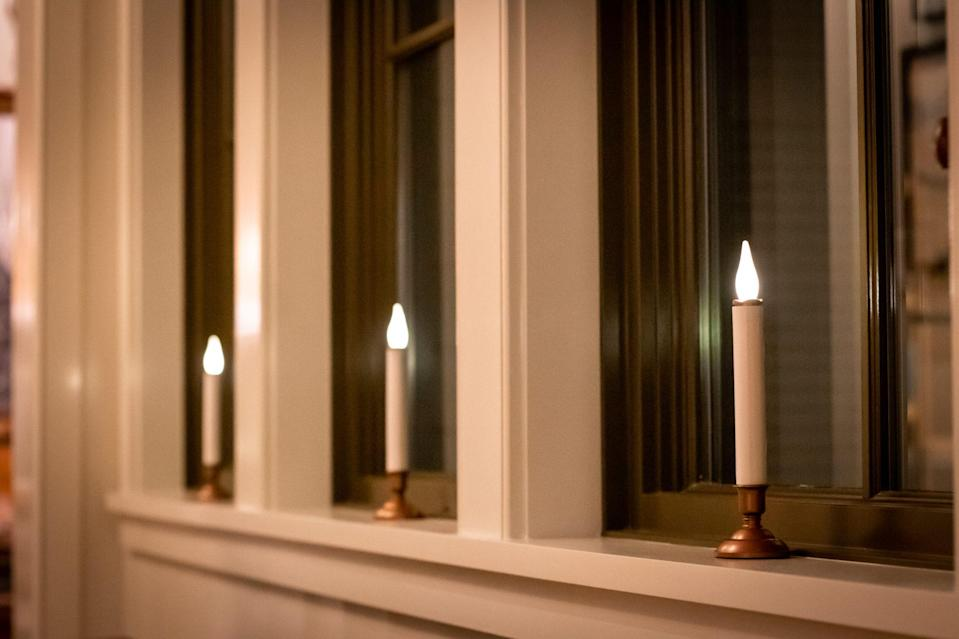 <p>Small spaces don't have to stay empty. Glowing in the windowsills, battery-operated flameless candles from The Home Depot (which can be seen from the street) add a cozy colonial Christmas look.</p>