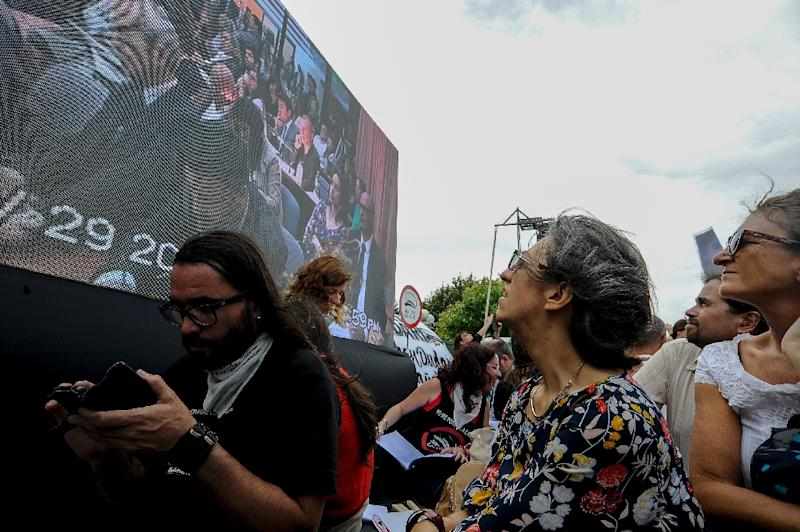 People follow the sentencing of former Argentine military personnel, who were jailed from eight years to life for human rights abuses, on a giant screen outside the courthouse (AFP Photo/Javier Gonzalez Toledo)