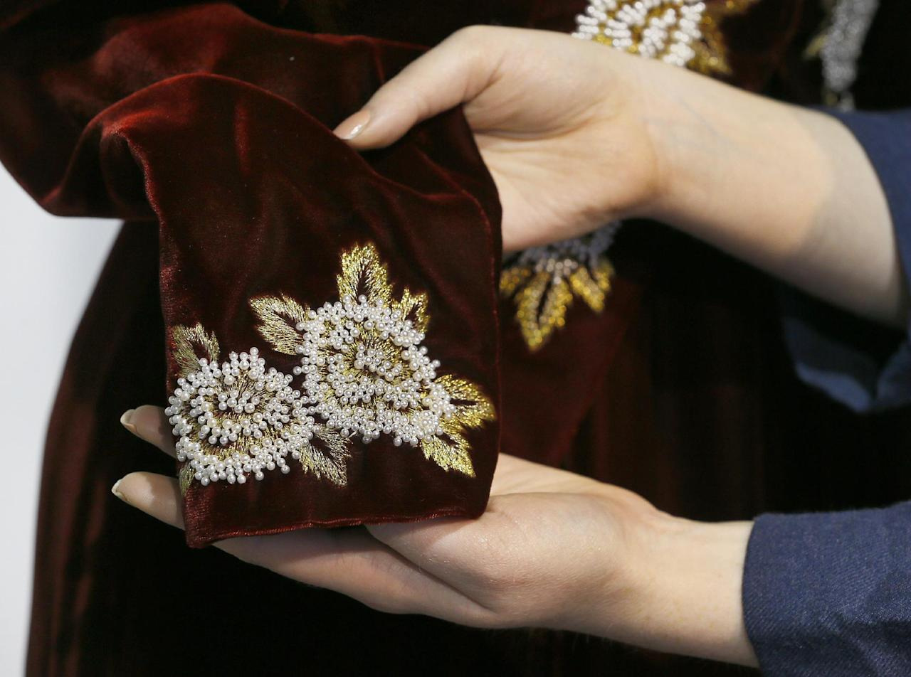 Beading detail is shown on a Catherine Walker burgundy velvet sheath with embroidered tailcoat worn for the State visit to Korea in 1992 by Britain's Princess Diana, at the Kerry Taylor auction rooms in London, Thursday, Feb. 28, 2013. The dress estimated to realise 40,000-60,000 pounds ( 62,000-93,000 US Dollars) will be sold in the Fit For a Princess auction in London on March 19. (AP Photo/Kirsty Wigglesworth)