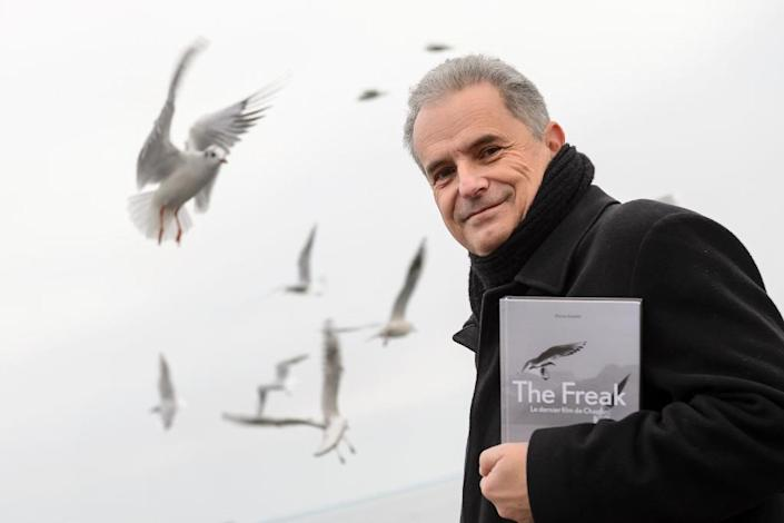 """Pierre Smolik poses with his book """"The Freak, the last film of Chaplin"""" on the edge of Lake Geneva, where English comic actor and filmmaker Charlie Chaplin liked to feed seagulls (AFP Photo/Fabrice Coffrini)"""