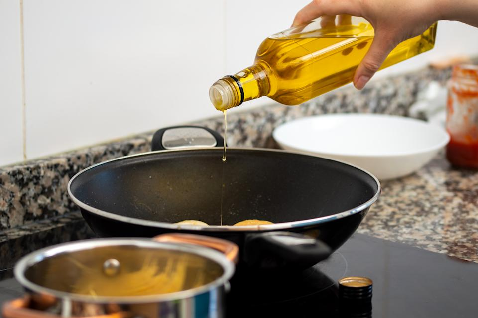 woman pouring cooking oil from bottle into frying pan on stove