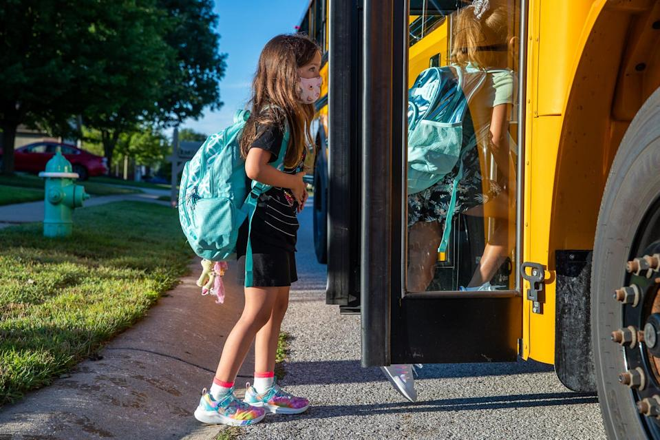 Third grader Hadley Steckler enters a school bus with other students on the way to Sycamore Elementary School in Avon, Ind.