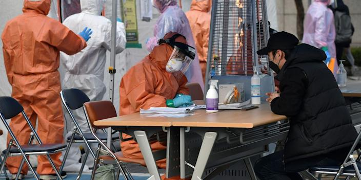 A medical staff member talks with a man at a testing facility in Seoul on March 4, 2020.