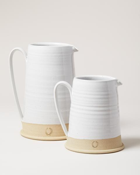 """<p><strong>Farmhouse Pottery</strong></p><p>farmhousepottery.com</p><p><strong>$165.00</strong></p><p><a href=""""https://www.farmhousepottery.com/collections/pitchers/products/countryman-pitcher?variant=11915907780"""" rel=""""nofollow noopener"""" target=""""_blank"""" data-ylk=""""slk:Shop Now"""" class=""""link rapid-noclick-resp"""">Shop Now</a></p><p>Thrown in <a href=""""https://www.farmhousepottery.com/"""" rel=""""nofollow noopener"""" target=""""_blank"""" data-ylk=""""slk:Farmhouse Pottery's"""" class=""""link rapid-noclick-resp"""">Farmhouse Pottery's</a> Vermont workshop, this pitcher looks just as beautiful serving mulled wine as it does a floral arrangement. </p>"""