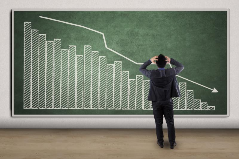 Man watching stock chart on chalkboard decline, has hands in hair, clearly stressed.