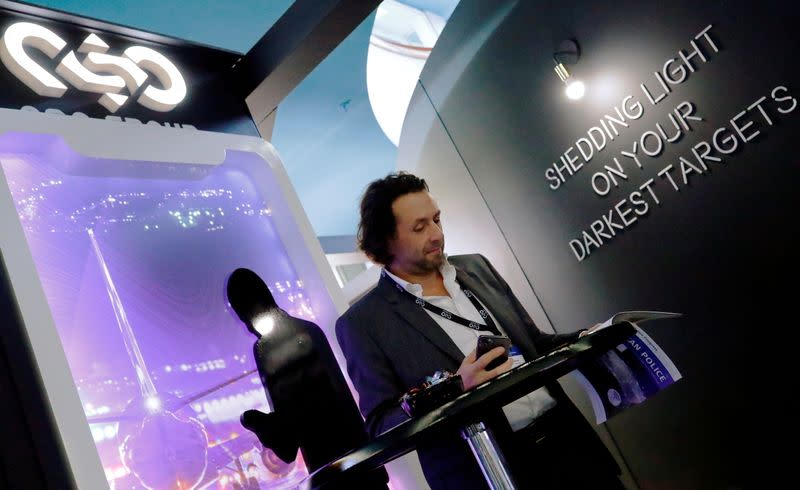 FILE PHOTO: A man reads at a stand of the NSO Group Technologies, an Israeli technology firm known for its Pegasus spyware enabling the remote surveillance of smartphones, at the annual European Police Congress in Berlin