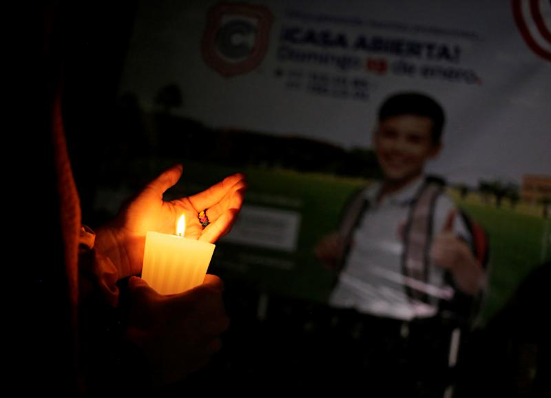 A woman holds a candle outside the Colegio Cervantes private school after a shooting in Torreon, Mexico January 10, 2020. REUTERS/Daniel Becerril