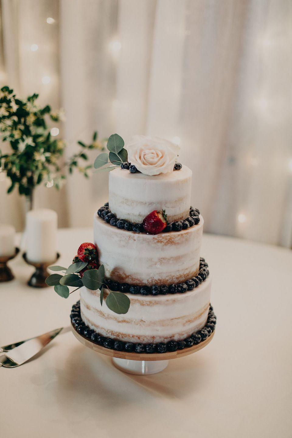 """<p>Who says berries are only for summer? Blueberries and strawberries look decadent on this fall wedding cake topped with <a href=""""https://www.fiftyflowers.com/"""" rel=""""nofollow noopener"""" target=""""_blank"""" data-ylk=""""slk:florals"""" class=""""link rapid-noclick-resp"""">florals</a>.</p>"""