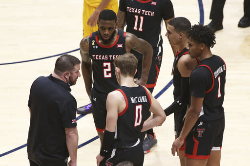 Texas Tech coach Chris Beard, left, speaks with players during the second half of an NCAA college basketball game against West Virginia, Monday, Jan. 25, 2021, in Morgantown, W.Va. (AP Photo/Kathleen Batten)