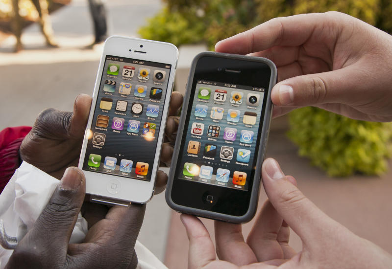 Noah Meloccaro, right, compares his older iPhone 4s to the new iPhone 5 held by Both Gatwech, outside the Apple Store in Omaha, Neb., Friday, Sept. 21, 2012 on the first day the iPhone 5 was offered for sale. (AP Photo/Nati Harnik)