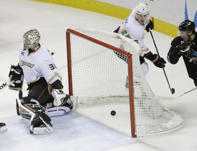 Anaheim Ducks goalie Frederik Andersen, of Denmark, is beaten for a goal by a shot from San Jose Sharks' Brent Burns, not seen, during the third period of an NHL hockey game Thursday, March 20, 2014, in San Jose, Calif. At right is Sharks' Joe Pavelski. San Jose won 3-2. (AP Photo/Marcio Jose Sanchez)