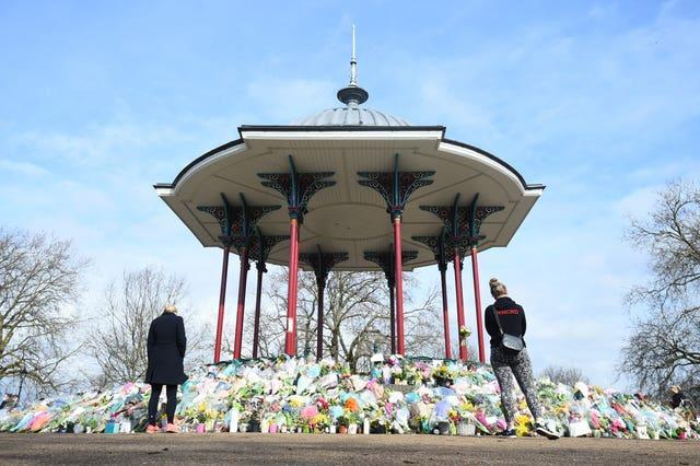 People stand next to floral tributes left at the band stand in Clapham Common for Sarah Everard