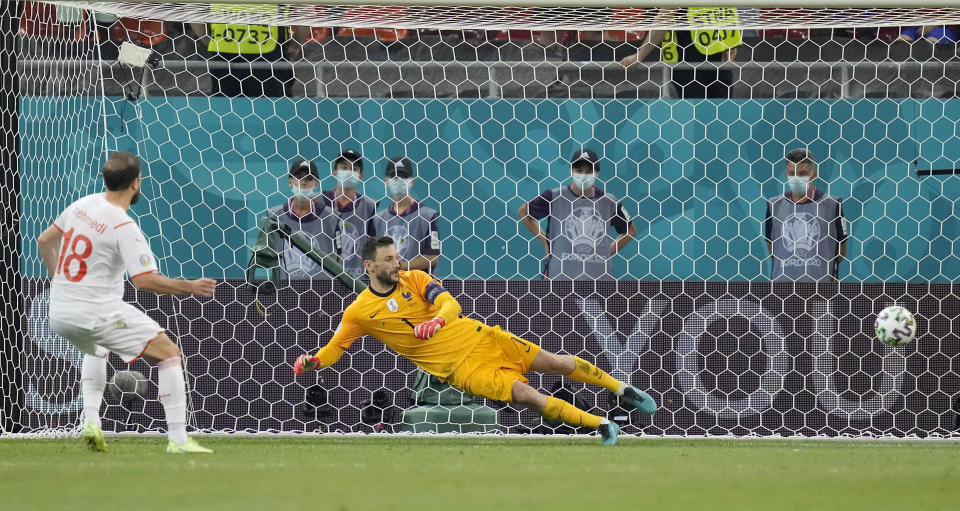 Switzerland's Admir Mehmedi, left, scores by penalty during the penalty shootout at the Euro 2020 soccer championship round of 16 match between France and Switzerland at the National Arena stadium in Bucharest, Romania, Tuesday, June 29, 2021. (AP Photo/Vadim Ghirda, Pool)