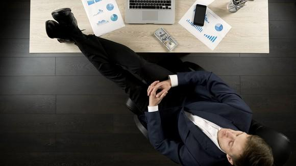 A businessman with his feet on his desk.